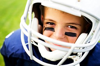 young boy of 10 years old smiling from a football helmet provided by HAVlife