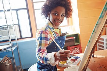 young girl smiling and painting in an art class funded by HAVlife